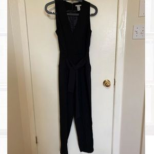 Black one piece pantsuit with belt and deep v-neck